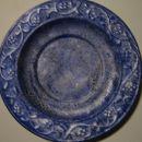 Krožnik iz keramike,spodaj pobarvan s srebrno barvo,zgoraj z modro in obrisano s krpo... e