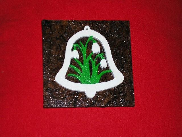 Spodaj vezena plošča oblečena v rižev papir, gor pa nalepljen lesen zvonček, še prej pobar