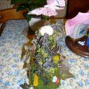 v mah, bršljan, nekaj suhega cvetja in nekaj vlitkov rožic obložen stožec iz stiroporja. T